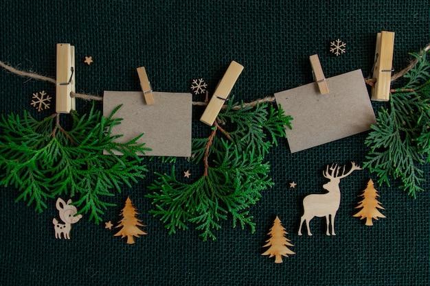Ano novo e ramos de composição de natal de uma árvore de natal e cartões pendurados em um fundo de corda ...