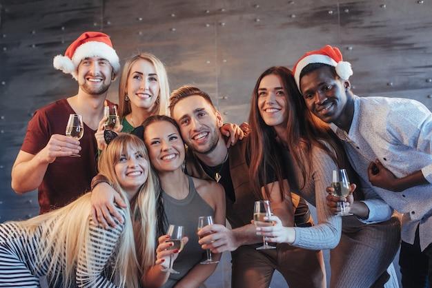 Ano novo está chegando! grupo de jovens alegres multiétnicas em chapéus de papai noel na festa, posando conceito de estilo de vida emocional das pessoas