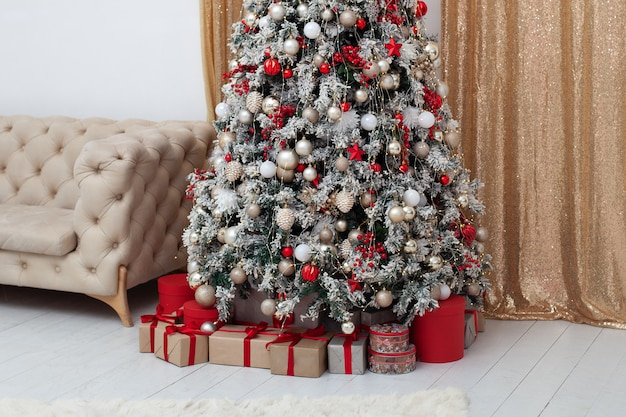 Ano novo. feliz natal, boas festas. interior da elegante sala de estar com árvore de natal decorada e sofá.