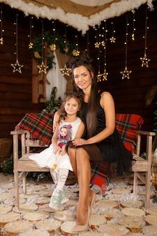 Ano novo . feliz natal, boas festas. uma menina de vestido branco, sentado no banco com a mãe. luz mágica no interior da árvore de natal à noite.
