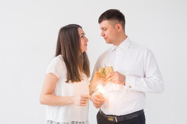 Ano novo, feriados, conceito de data - casal apaixonado segurando luz de estrelinhas e taças de champanhe na parede branca