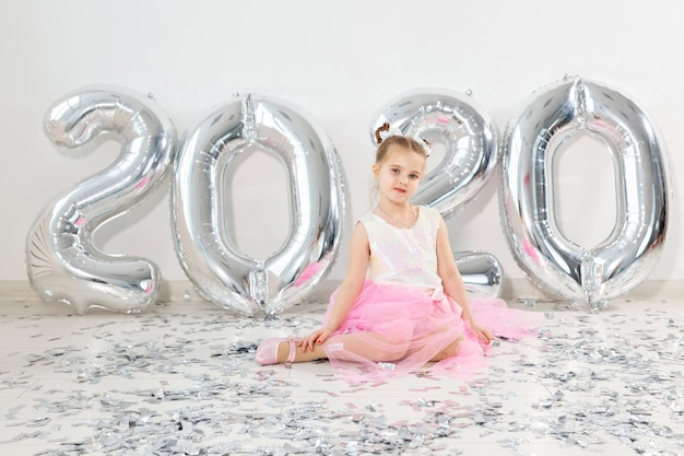 Ano novo, feriados e celebração conceito - uma menina sentada perto com números balões 2020