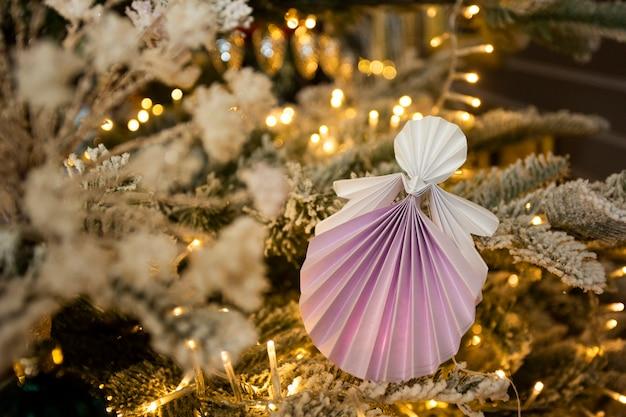 Ano novo figuras de origami papercraft anjo artesanal na árvore de natal com decorações interiores de férias com luzes quentes. natal neve árvore conceito inverno cartão estúdio tiro close-up