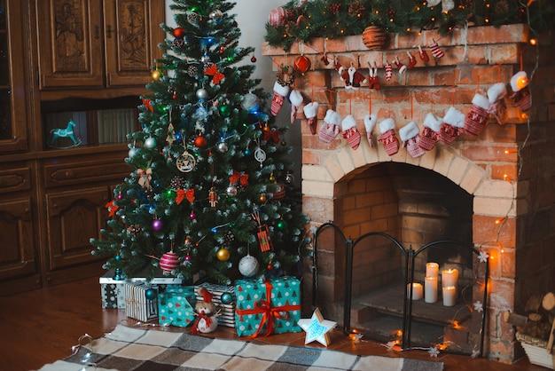 Ano novo interior festivo. árvore de natal decorada junto à lareira.