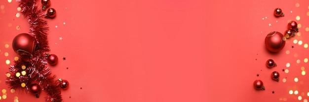 Ano novo ou cartão de natal com bolas vermelhas brilhantes e enfeites de natal em um fundo vermelho com copyspace