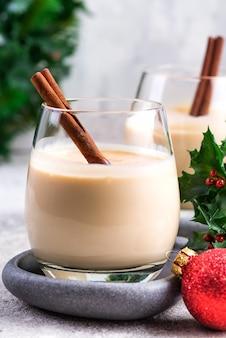 Ano novo ou coquetel de gemada de natal com canela e noz-moscada em um copo, galhos de bagas de azevinho e bola brinquedo na pedra clara, decoração festiva
