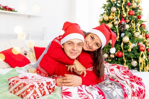 Ano novo ou natal, um casal feliz e apaixonado, um homem e uma mulher na cama em casa perto da árvore de natal de suéteres vermelhos sorrindo, se abraçando e se beijando parabenizando pelo feriado