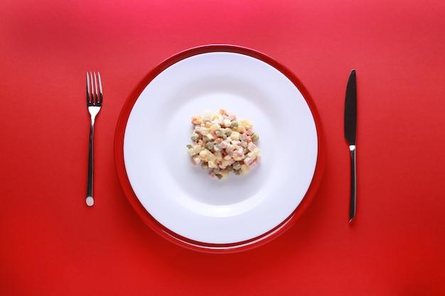 Ano novo russo ou salada de natal em fundo vermelho.