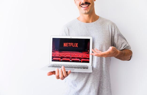 Anônimo homem sorridente mostrando laptop com o logotipo da netflix