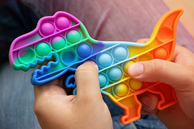 Anonymus adulto segura nas mãos um novo brinquedo de silicone em forma de dinossauro brinquedo antiestresse sensorial