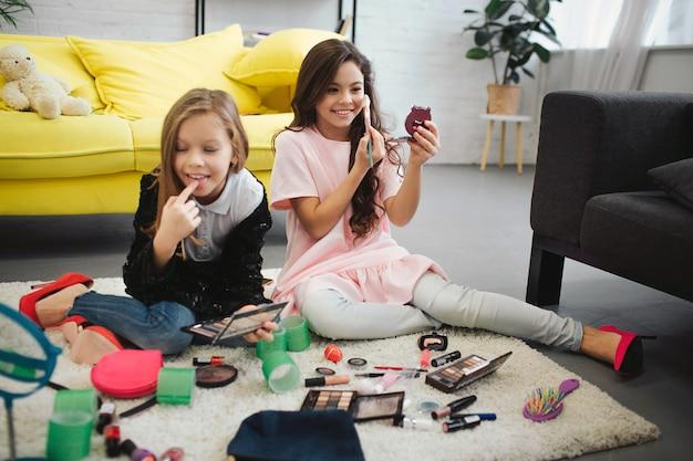 Ans alegre saiu meninas sentado no chão na sala. eles estão fazendo maquiagem. os adolescentes se olham no espelho e usam cosméticos.