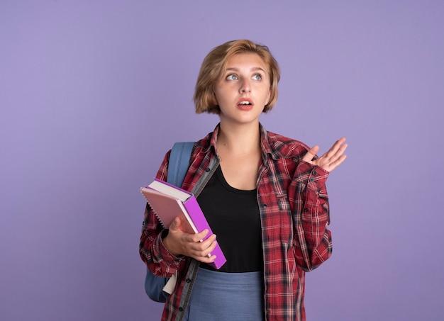 Ansiosa aluna eslava usando uma mochila ereta com a mão levantada segurando um livro e um caderno olhando para o lado