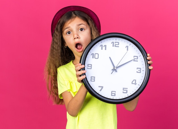 Ansiosa garotinha caucasiana com chapéu de festa roxo segurando um relógio isolado na parede rosa com espaço de cópia