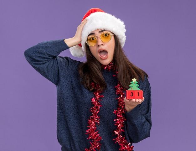 Ansiosa jovem caucasiana em óculos de sol com chapéu de papai noel e guirlanda em volta do pescoço coloca a mão na cabeça e segura o enfeite de árvore de natal isolado na parede roxa com espaço de cópia