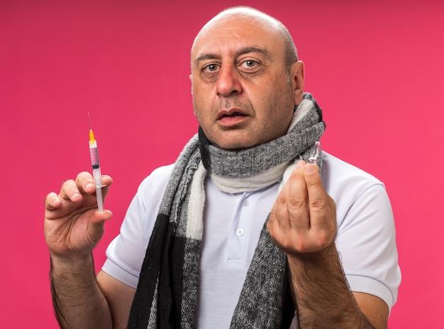 Ansioso adulto doente caucasiano com um lenço no pescoço segurando uma seringa e uma ampola isolada na parede rosa com espaço de cópia