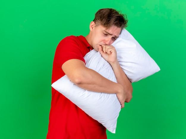 Ansioso jovem bonito loiro doente abraçando o travesseiro e caughing
