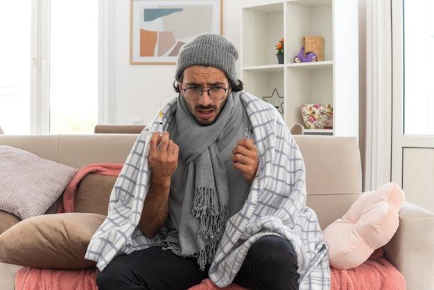 Ansioso jovem doente com óculos óticos embrulhado em xadrez com lenço no pescoço, chapéu de inverno segurando uma ampola médica e olhando para uma seringa sentado no sofá da sala de estar