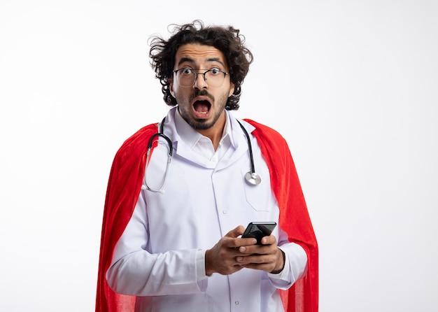 Ansioso jovem super-herói caucasiano com óculos ópticos, uniforme de médico com capa vermelha e estetoscópio no pescoço segura o telefone e parece com espaço de cópia