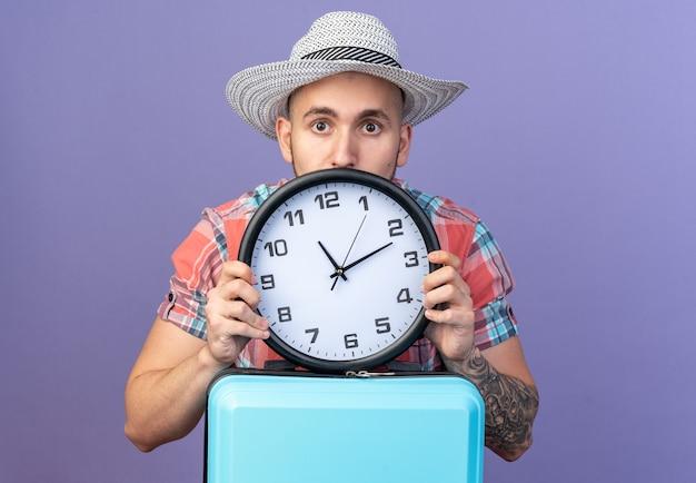 Ansioso jovem viajante com chapéu de palha de praia segurando um relógio atrás da mala, isolado na parede roxa com espaço de cópia