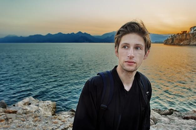 Antalya, no início da temporada turística no início da primavera, jovem branco passeia perto do mar ao pôr do sol