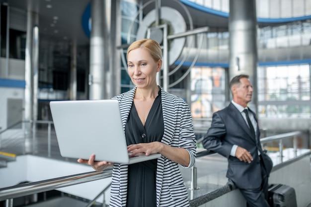 Antecipação. mulher de negócios sorridente em pé olhando para um laptop e um homem em um terno formal com uma mala atrás no aeroporto