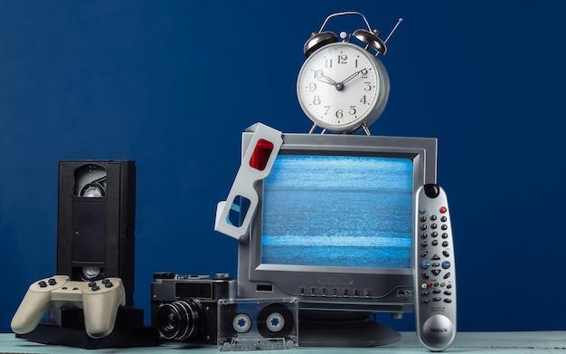 Antena antiquado receptor de tv retro, óculos anáglifos, relógio, cassete de áudio e vídeo, gamepad, câmera, controle remoto em azul clássico.