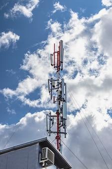 Antena celular contra um céu azul nublado em uma área residencial. tecnologias de comunicação modernas.