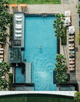 Antena da piscina com bar flutuante, as pessoas se deitam nas cadeiras de praia e um homem nadando no verão.