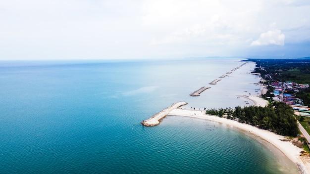 Antena da praia com vista do quebra-mar através da linha de costa e grupo de pessoas e pequeno barco de pesca na praia de areia branca, árvores e água do mar clara.