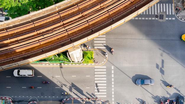 Antena da vista superior de um carro de condução na faixa de asfalto e faixa de pedestres na estrada de tráfego com silhueta de luz e sombra com trem do céu ferroviário.