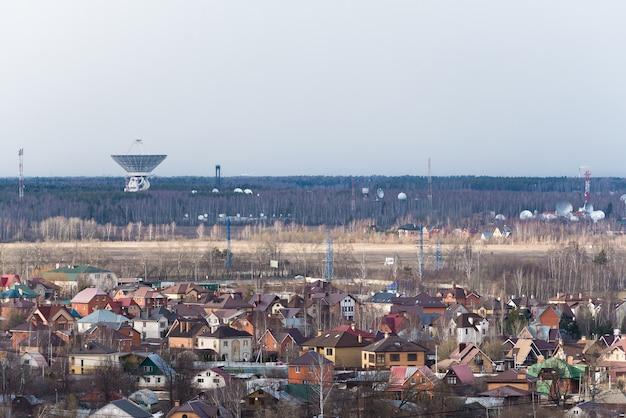 Antena de satélite no campo do centro de comunicação espacial próximo à área residencial