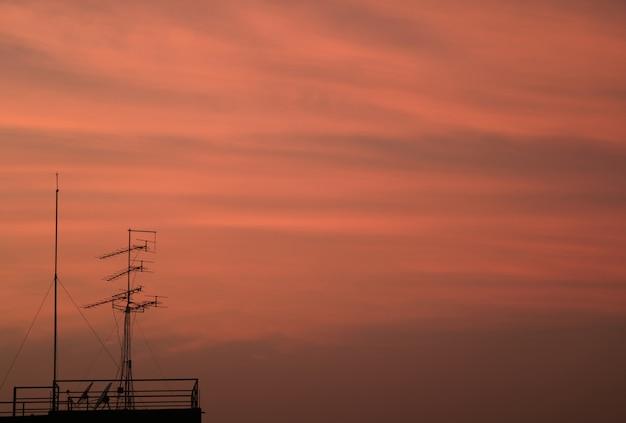 Antena de tv contra o lindo céu nublado rosa no crepúsculo de bangkok, tailândia