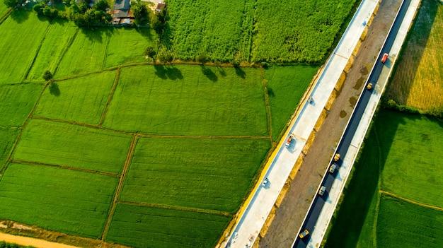 Antena do campo verde e da estrada asfaltada na vista superior.