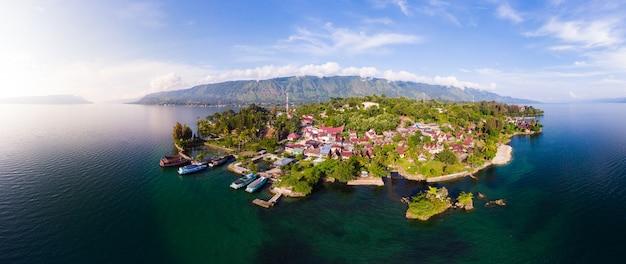 Antena: lago toba e samosir island ver os de cima de sumatra indonésia. enorme caldeira vulcânica coberta por água, aldeias tradicionais de batak, arrozais verdes, floresta equatorial.