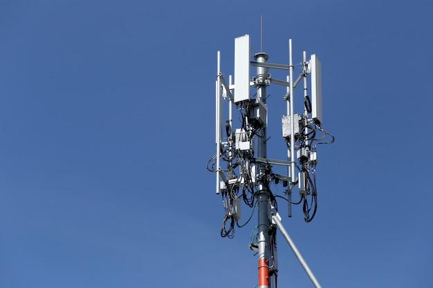 Antena para comunicações do telefone no tempo brilhante do dia do céu.