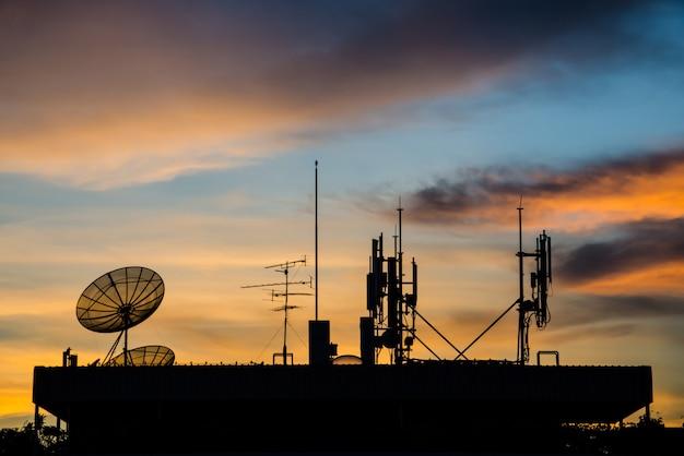 Antena parabólica e telecom torre ao pôr do sol