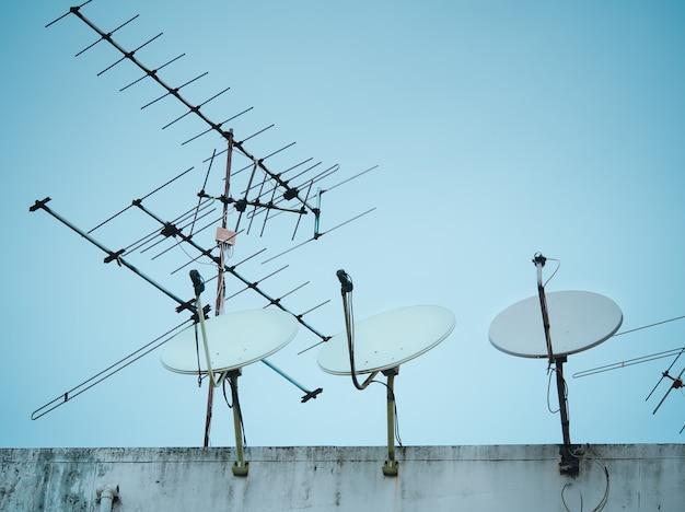 Antena parabólica home e antena da tevê sobre a construção, banguecoque, tailândia.