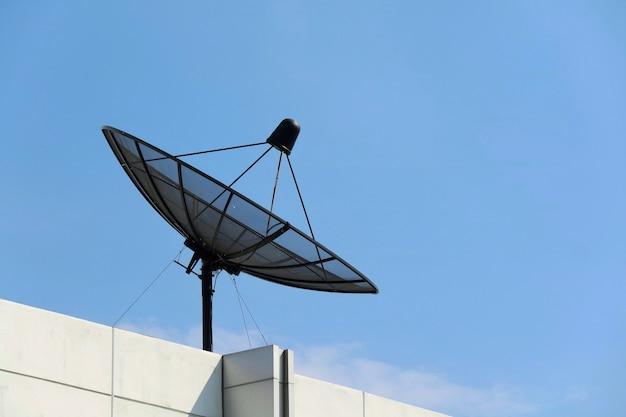 Antena parabólica no topo do telhado do prédio com a superfície do céu azul