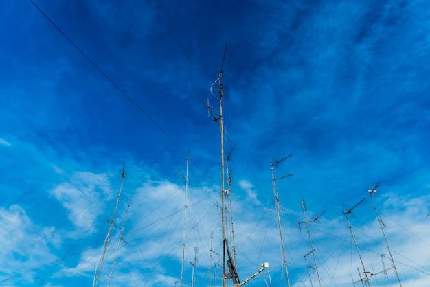 Antenas de televisão no telhado de um edifício velho com céu dramático.
