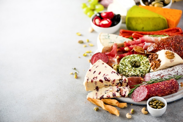 Antepasto italiano tradicional, tábua de cortar com salame, carne defumada fria, presunto, presunto, queijos, azeitonas, alcaparras