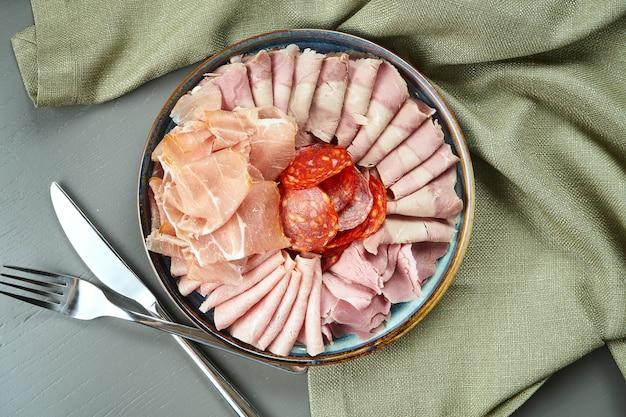Antepastos de carne italiana de luxo para vinho na placa cerâmica na mesa de madeira, vista superior em salame, presunto, presunto e chouriço