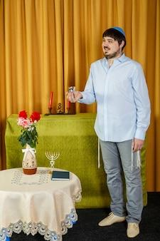 Antes da cerimônia da chupá, o noivo judeu na sinagoga segura uma taça de kidush com vinho. foto vertical