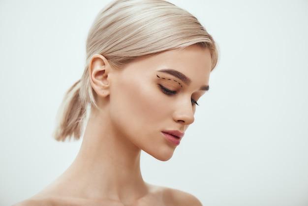 Antes da cirurgia facial, vista lateral de uma jovem loira com desenho no rosto