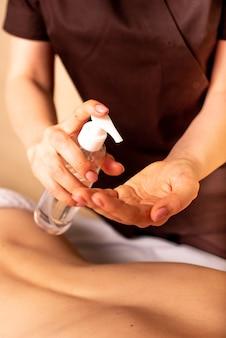 Antes da massagem, o massagista aplica um spray de óleo nas mãos