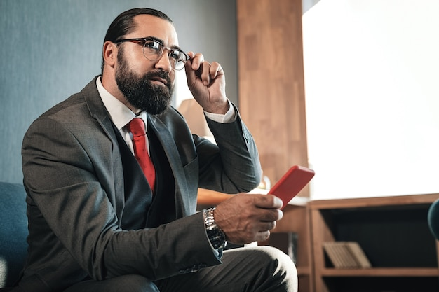 Antes da negociação. homem de negócios rico e barbudo de cabelos escuros se sentindo animado antes de negociar com o investidor