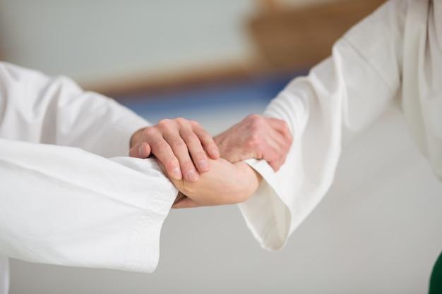 Antes de começar a luta. menino e seu professor profissional de aikido apertando as mãos antes de começar a luta