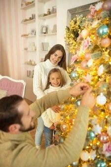 Antes do natal. papai jogando bolas na árvore de natal enquanto sua esposa e filha o observam