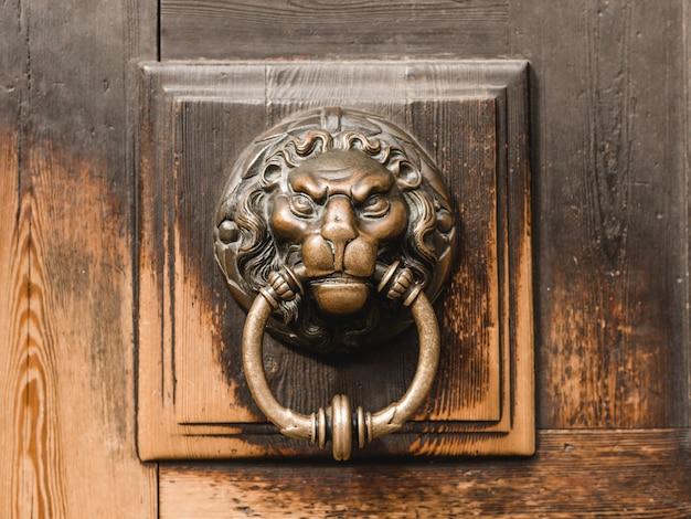 Antiga aldrava de latão em forma de cabeça de leão, detalhe de porta de madeira