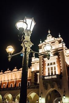 Antiga área comercial de cracóvia à noite, à luz dos candeeiros de rua. velha europa.