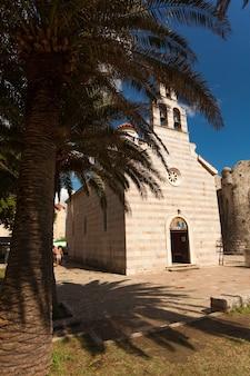Antiga basílica ortodoxa bonita e palmeira crescendo ao lado dela